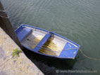 Small blue rowing boat tied up in harbour
