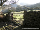 Metal gate in stone wall with mountains behind