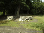 Round stone walled structure in woodland